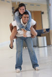 Portrait of two college students piggyback Stock Photos