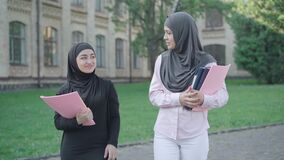 Portrait of two confident Muslim women walking on university yard and talking. Young female immigrants studying in