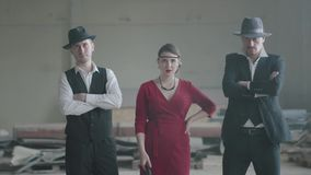 Portrait two confident well-dressed men standing in two sides of a woman in red dress, who is aiming a pistol at the. Two confident well-dressed men standing in stock footage