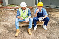 Construction Workers on Lunch Break. Portrait of two construction workers taking break on site eating lunch out of plastic containers outdoors Royalty Free Stock Photo