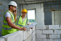 Two Workers with Floor Plans. Portrait of two construction workers wearing hardhats discussing floor plans inside unfinished  building Stock Photo