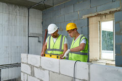 Construction Workers Building Wall. Portrait of two construction workers wearing hardhats and reflective vests  checking concrete block wall using level Royalty Free Stock Photography