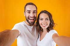 Portrait of two contented people man and woman smiling while taking selfie photo, isolated over yellow background. Portrait of two contented people men and women stock images