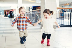 Portrait of two cute adorable babies children kids toddlers friends siblings running in mall store. Laughing smiling holding hands, going shopping royalty free stock photo