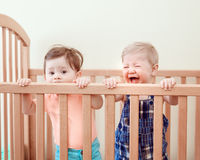 Portrait of two cute adorable funny babies siblings friends of nine months standing in bed crib chewing eating sucking wooden side Stock Images