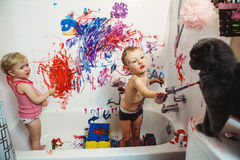 Portrait of two cute adorable white Caucasian little boy and girl playing painting cat with paints in bathroom Royalty Free Stock Photo