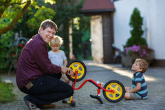 Portrait of two cute boys repairing bicycle wheel with father ou Royalty Free Stock Photos