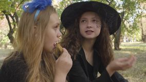 Portrait of two cute caucasian girls in Halloween costumes eating cookies in the autumn forest. Portrait of two cute caucasian girls in Halloween costumes stock video