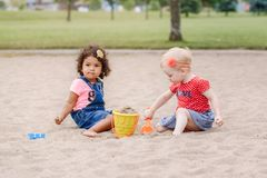 Two cute Caucasian and hispanic latin toddlers babies children sitting in sandbox playing with plastic colorful toys. Portrait of two cute Caucasian and hispanic royalty free stock image