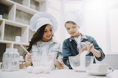 Portrait of Two Cute Children Cooking at Kitchen. Caucasian Boy and Girl Wearing Casual Clothes and Hats Make Cookies Posing with Cheerful Expression. Happy stock images