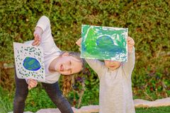 Portrait of the two cute little girls holding the drawing earth globe.Kids paintig picture of earth having fun outdoor. royalty free stock images