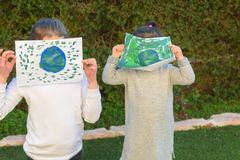 Portrait of the two cute little girls holding the drawing earth globe.Kids paintig picture of earth having fun outdoor. stock photography