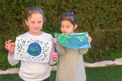 Portrait of the two cute little girls holding the drawing earth globe.Kids paintig picture of earth having fun outdoor. stock images