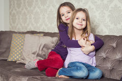 Portrait of two cute sisters at home. Family Stock Photos