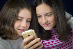 Portrait of two cute sisters looking at cell phone Stock Photos
