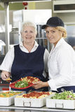 Portrait Of Two Dinner Ladies In School Cafeteria Stock Photos