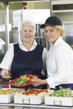 Portrait Of Two Dinner Ladies In School Cafeteria stock photos