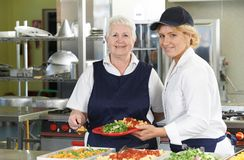 Portrait Of Two Dinner Ladies In School Cafeteria royalty free stock photography