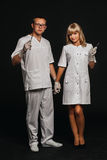 Portrait two doctors wearing white medical uniform holding a pair of scissors and tweezers in both hands Royalty Free Stock Photography