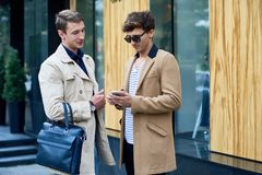 Two Stylish Men Chatting Outdoors. Portrait of two elegant young businessmen wearing autumn coats chatting outdoors in city streets, copy space royalty free stock image