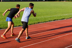 Portrait of two energetic sportsmen running on stadium track. Outdoors on sunny day stock images