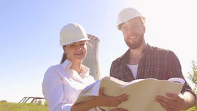 Portrait of two engineers in helmet with drawings. Portrait of two architects with drawings in their hands looking at the camera stock footage