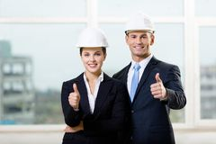 Portrait of two engineers thumbing up. Portrait of two engineers standing near each other and thumbing up Stock Image