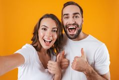 Portrait of two european people man and woman smiling while taking selfie photo, isolated over yellow background stock photo
