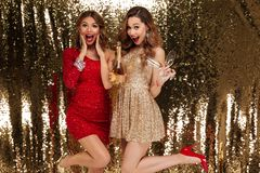 Portrait of two excited attractive girls in shiny dresses. Holding bottle of champagne and glasses while standing and celebrating isolated over golden shiny Royalty Free Stock Images