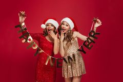 Portrait of two excited attractive women. In sparkly dresses looking at camera while standing and holding happy new year ribbon isolated over red background royalty free stock image