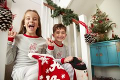 Portrait Of Two Excited Children Wearing Pajamas Sitting On Stairs Holding Stockings On Christmas Morning stock images
