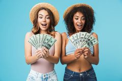 Portrait of two excited women with different type of skin wearing straw hats and summer clothing looking at lots of money holding. In hands over blue background royalty free stock photography