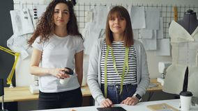 Portrait of two female clothing designers entrepreneurs standing in workshop together and looking at camera. One woman. Portrait of two young female clothing stock video footage