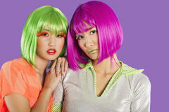 Portrait of two female friends wearing wigs against gray background Stock Photo
