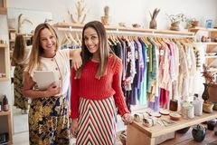 Portrait Of Two Female Sales Assistants With Digital Tablet Working In Clothing And Gift Store royalty free stock photo