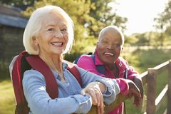 Portrait Of Two Female Senior Friends Hiking In Countryside royalty free stock photography