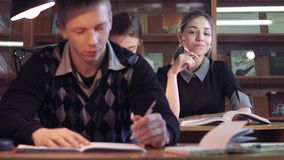 Portrait of two female students discussing their books and a boy studying. Portrait of two female students discussing their books and a boy focused on studying stock video
