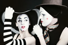 Portrait of two flirting mimes on a black background Royalty Free Stock Photos