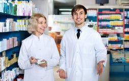 Portrait of two friendly pharmacists working farmacy Stock Photos