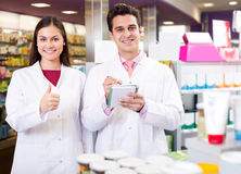 Portrait of two friendly pharmacists working Stock Photos
