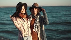 Portrait of two friends on the background of autumn sea. beautiful girl smiling and happy. Two cute young women are smiling and enjoying life on an autumn walk stock footage