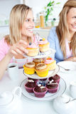 Portrait of two friends eating pastries in the ki Stock Photo