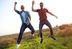 Portrait of two friends jumping in field. Royalty Free Stock Image