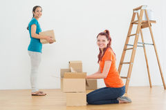 Portrait of two friends moving together in a new house Royalty Free Stock Photos