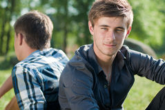 Portrait of Two friends outdoors back to back. Portrait of Handsome young men sitting back to back on the field of green grass outdoors on a bright sunny day of Royalty Free Stock Images
