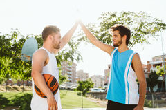 Portrait of two friends playing basketball on court. Stock Image
