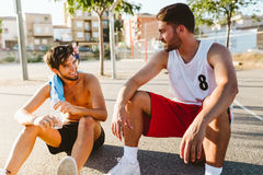Portrait of two friends relaxing after playing basketball on cou Royalty Free Stock Image