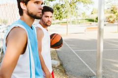 Portrait of two friends relaxing after playing basketball on cou Royalty Free Stock Photos