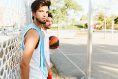 Portrait of two friends relaxing after playing basketball on cou Stock Photos