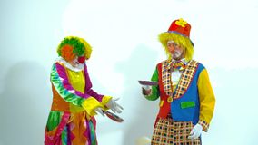 Portrait of two funny clowns playing with pans and false-cakes stock footage